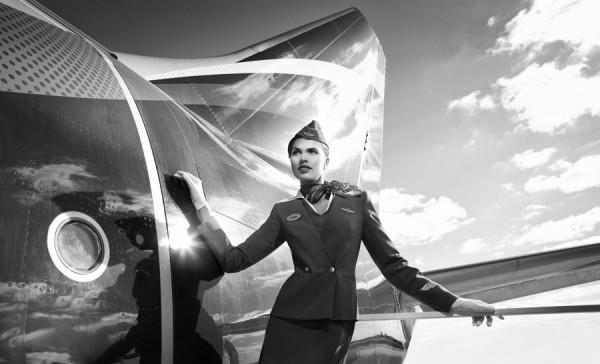 Стюардесса в шляпке-пилотке на фоне самолета. Фото Аэрофлота.