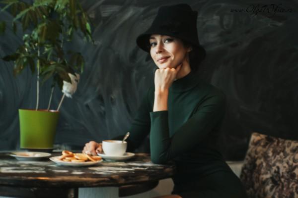 Черная фетровая шляпа с опущенными полями к зеленому платью